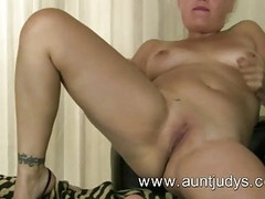 Kelly strips and finger fucks her shaved pussy. Thumb